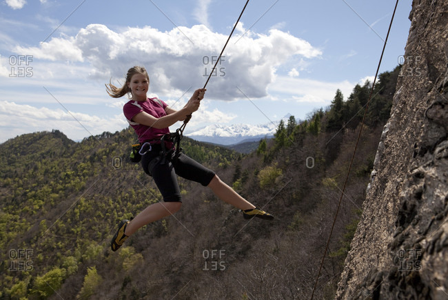 Teen girl swings out from rock while climbing