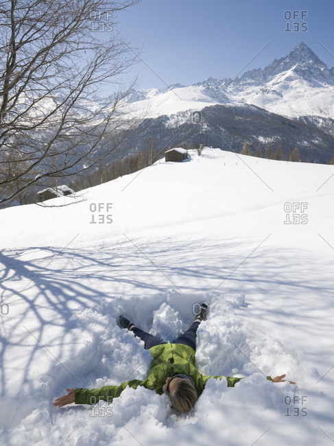 Woman makes snow angel in mountain meadow