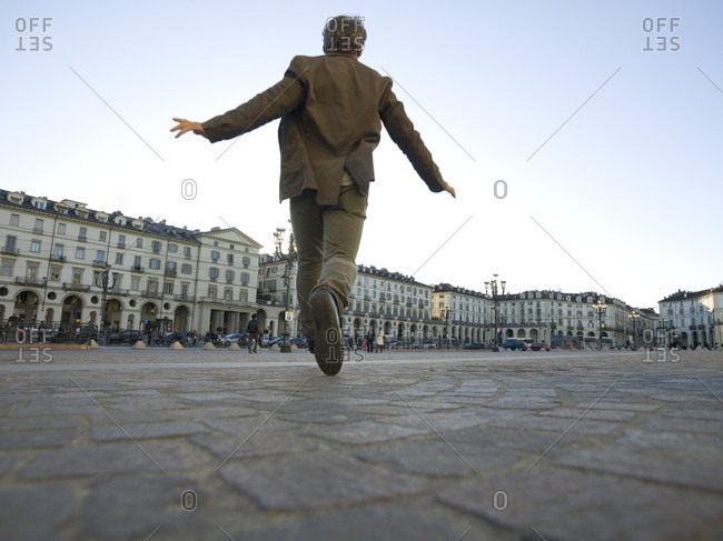 Piedmont, Piedmont, Italy - March 26, 2010: Low angle view of man running thru piazza