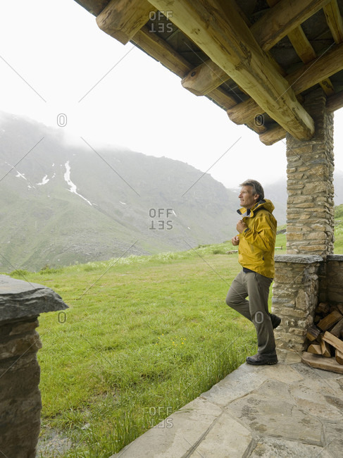 Hiker zips up raincoat leaving shelter in mountains