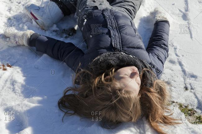 Teen girl reclines in snowy meadow