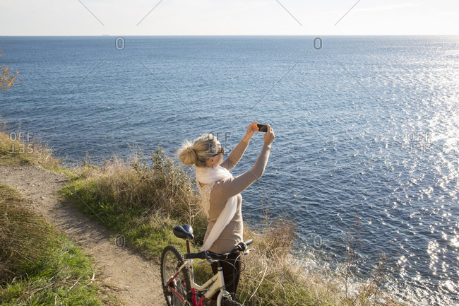 Woman with bike takes photo above the sea