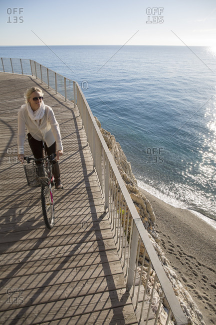 Elevated perspective of woman riding bike by sea