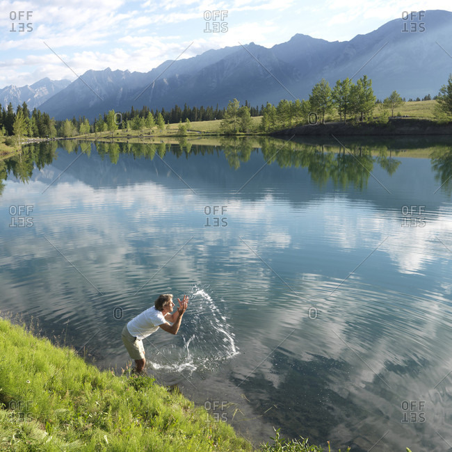 Man refreshes himself in mountain lake