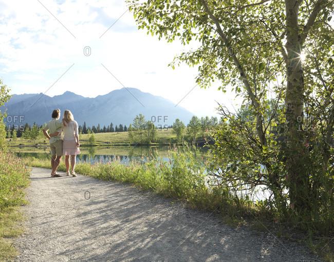 Couple walk along trail by mountain lake
