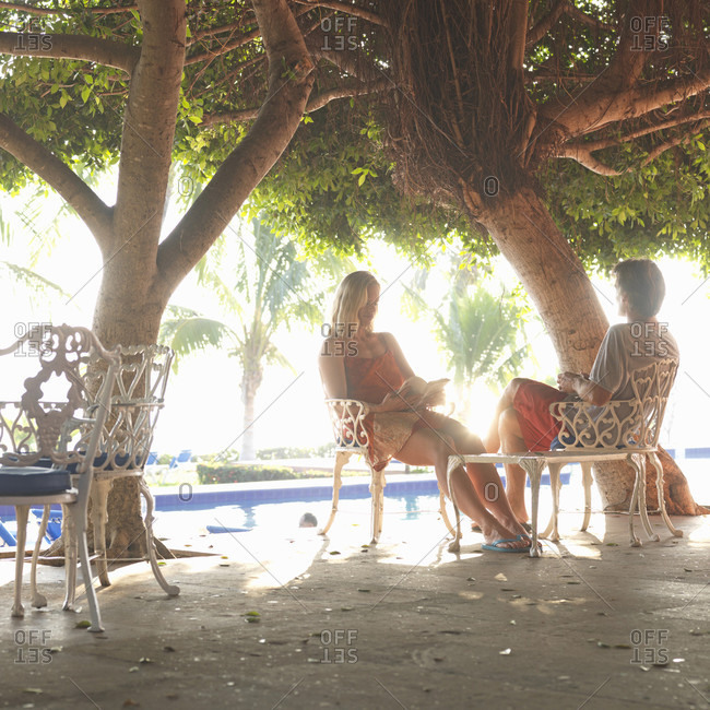 Couple relax on outdoor patio under tree