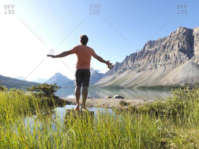 Man balances on rock above alpine lake