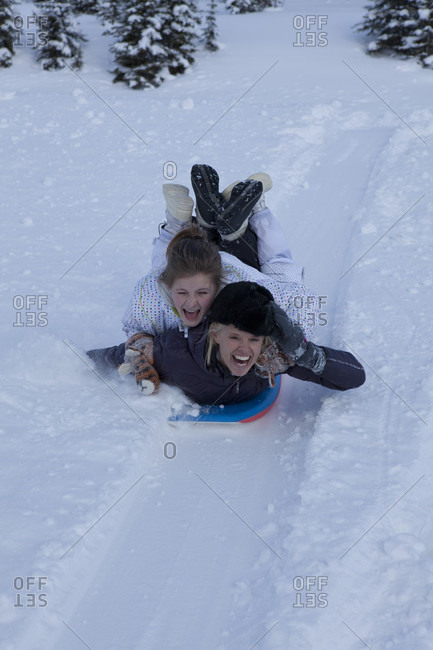 View towards mother and daughter sliding down hill together