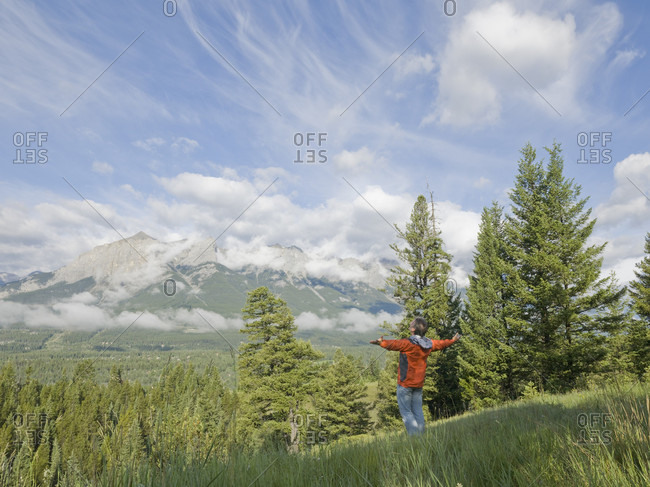 Man celebrates over forest, mountains and clouds