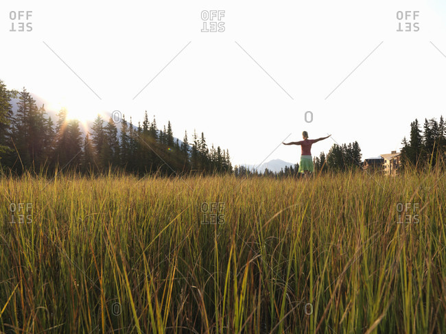 View across meadow grasses to woman