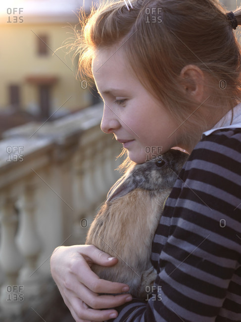 Tween girl snuggles pet rabbit