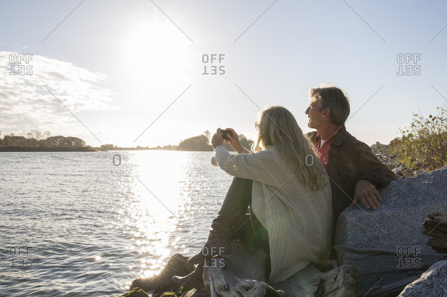 Couple take photo of sunrise over delta from rocky shoreline