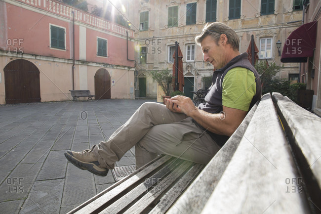 Hiker writes message on cell phone in piazza