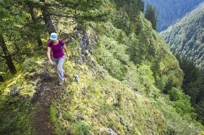 A Woman Walks Up A Narrow Trail With A Steep Drop Into A Green Valley Below
