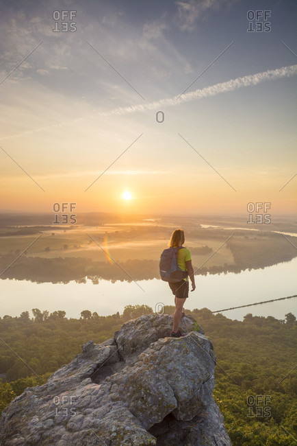 Woman standing on sandstone overhang watching sunrise from summit of Petit Jean Mountain above Arkansas River Valley