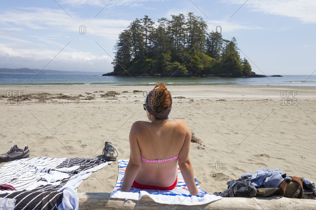 A Young Woman Relaxing On Beach Near Tofino, Vancouver Island, British Columbia