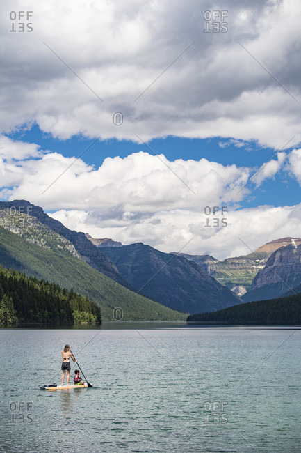 Woman Paddleboarding With Child In Bowman Lake At Glacier National Park