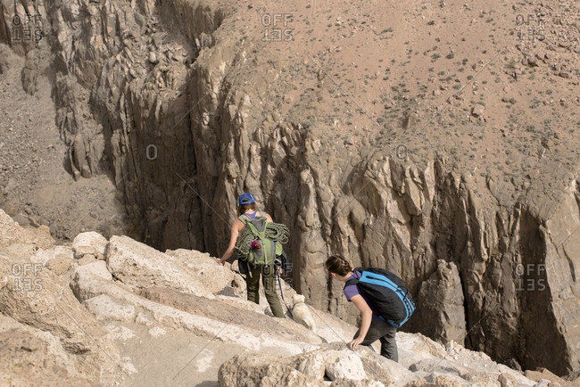 Two Female Climbers Begin A Steep Decent Into Owens River Gorge In Bishop, California, Usa