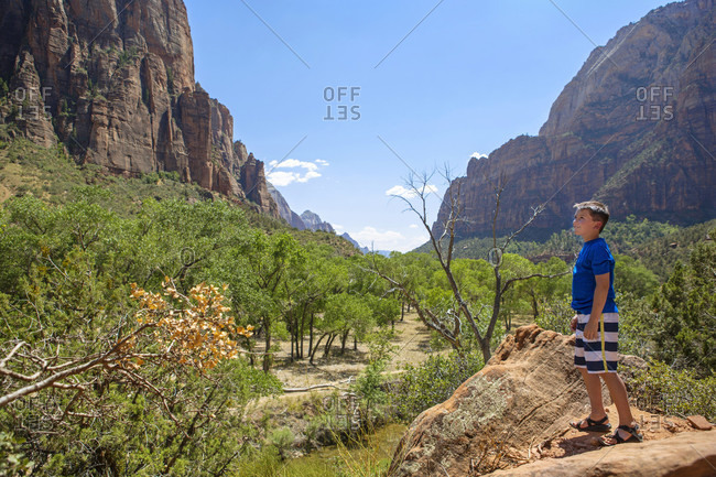 A Young Boy Hikes A Trail In Zion Canyon National Park