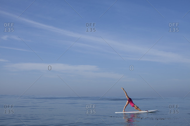 A Woman Doing Yoga On Her Stand-Up Paddleboard In The Pacific Ocean, San Diego Coast, California