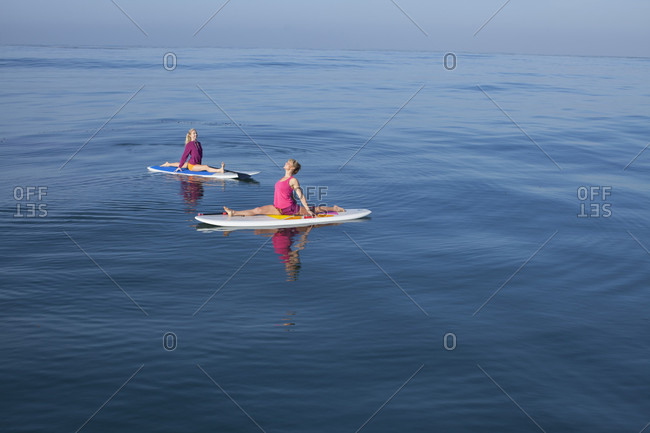 Two Women Doing Yoga On Their Stand-Up Paddleboards On The Pacific Ocean, San Diego