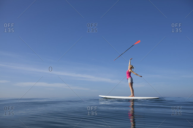 A Woman Tossing A Paddle In The Air Standing On Her Stand-Up Paddleboard On The Pacific Ocean, San Diego, California