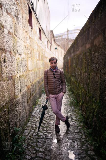 Man with umbrella in cobblestone alley