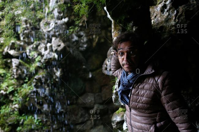 Man in grotto below waterfall