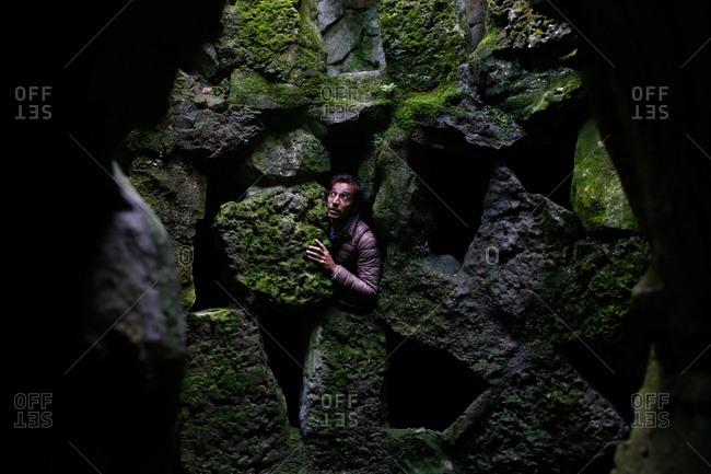 Man peeking out of stone ruins
