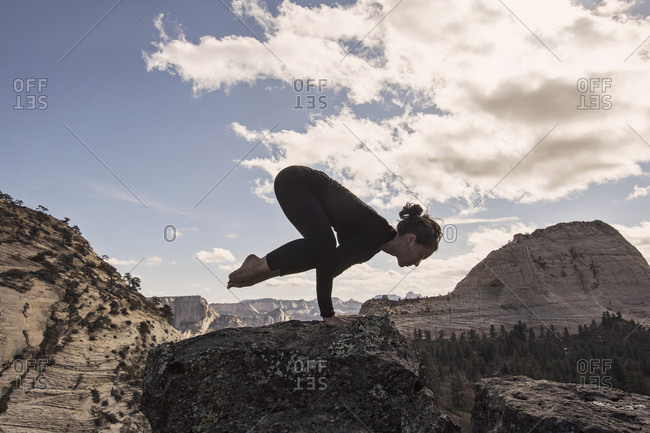 A Woman Practices Yoga In Zion National Park, Utah
