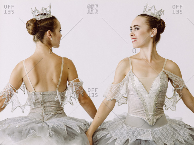 Two ballet dancers standing side by side but opposite of each other
