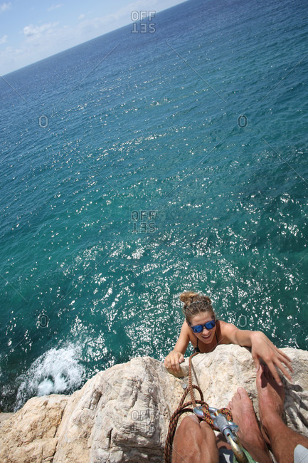 POV to young woman climbing vertical rock above sea