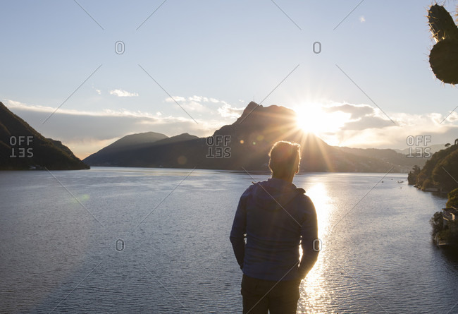 Mature man watches sun rising over mountain and lake