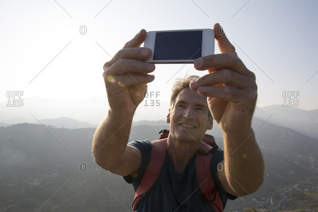POV of mature man taking selfie with phone in mountains