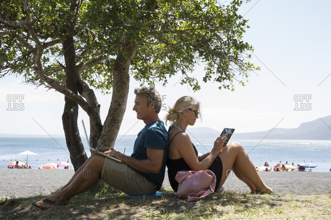 Mature couple sit in shade on lakeshore using computer and tablet