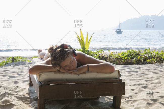 Young woman relaxes on beach, listens to music