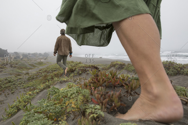 Detail of woman's foot and distant man, foggy coastline