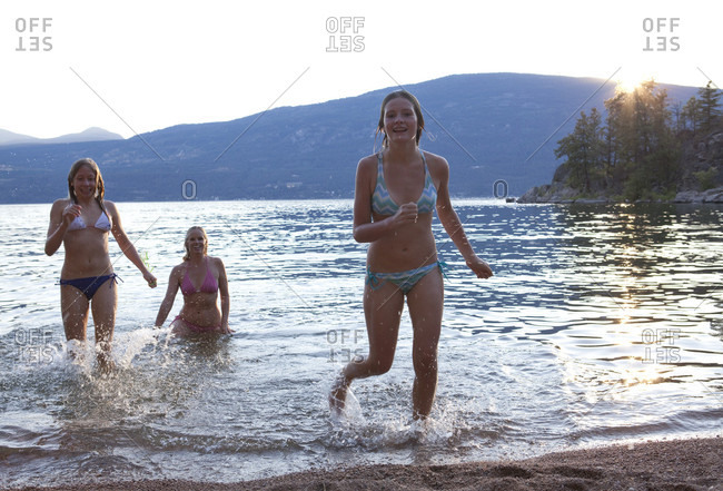 Three girls run out of lake at sunset
