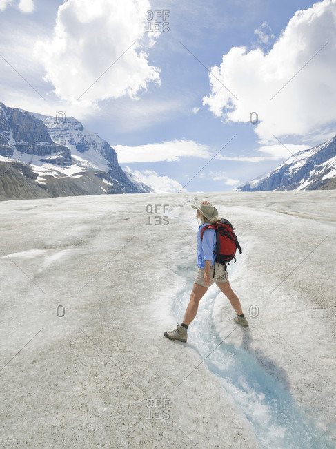 Hiker straddles glaciel stream on glacier