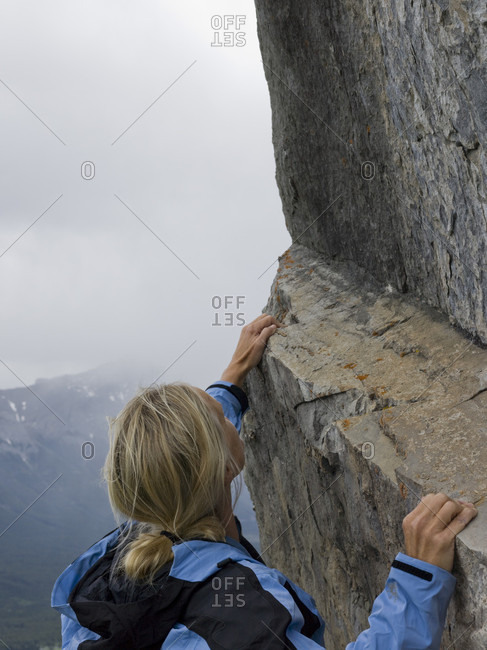 Portrait of woman climbing steep rock face