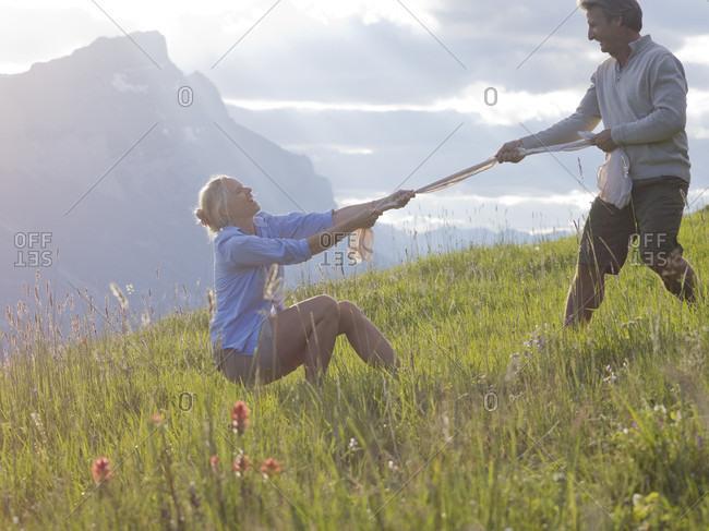 Woman and man play tug-o-war in mountain meadow stock photo