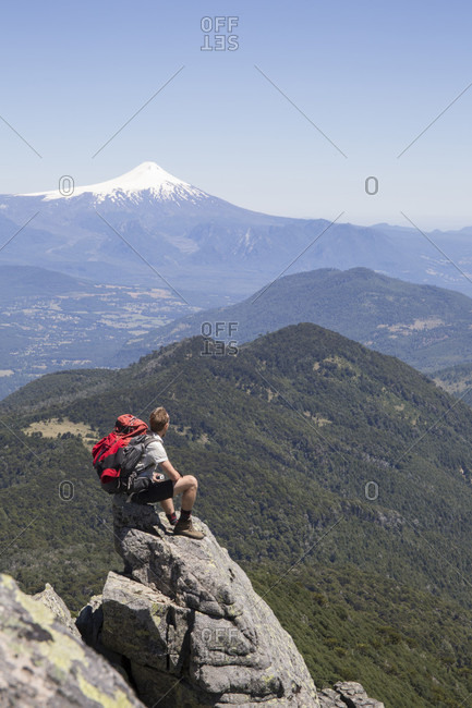 Hiker sits on rock promentory with volcano in distance