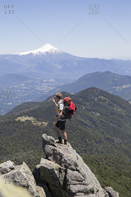 Hiker takes photo on summit in front of volcano