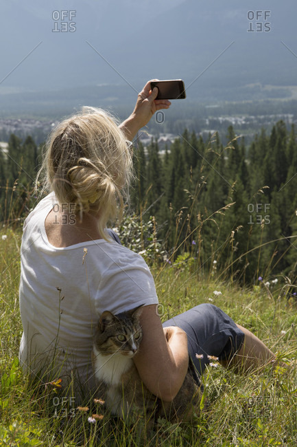 Woman takes photo with cat in mountain meadow