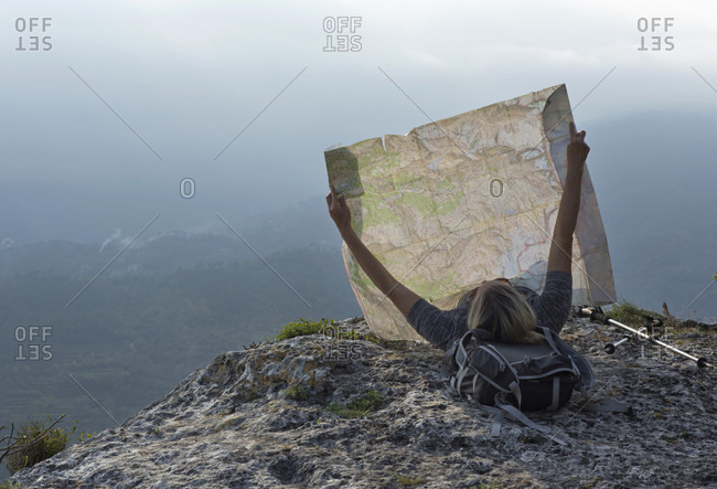 Mature woman hiker reclines on cliff edge with map