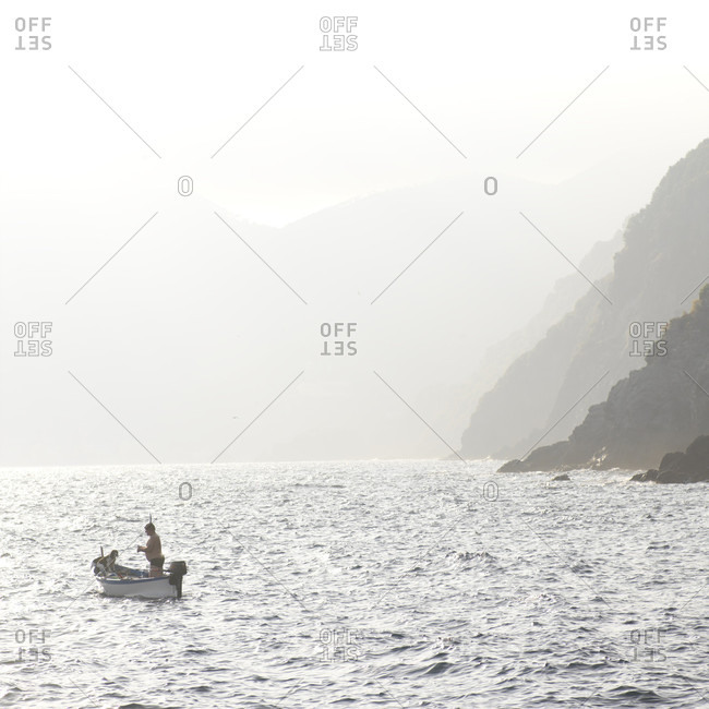 Fisherman and dog in boat on choppy sea, mountains behind