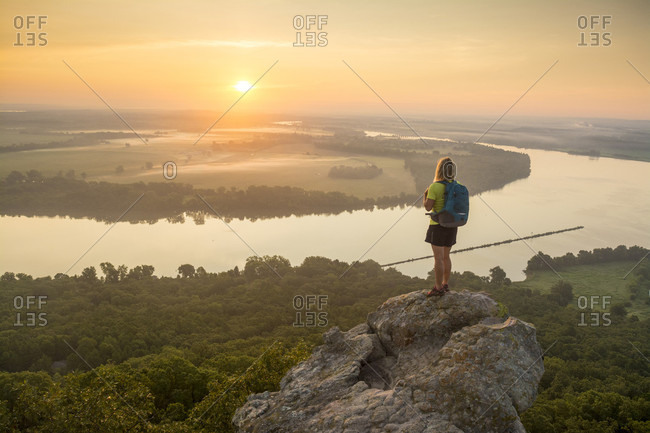 Woman standing on sandstone overhang watching sunrise from summit of Petit Jean Mountain Above Arkansas River Valley?