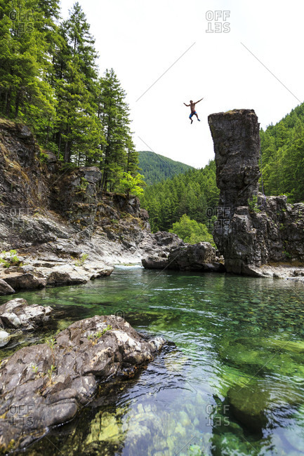 Man Leaping Into A Crystal Clear Pool From Rock