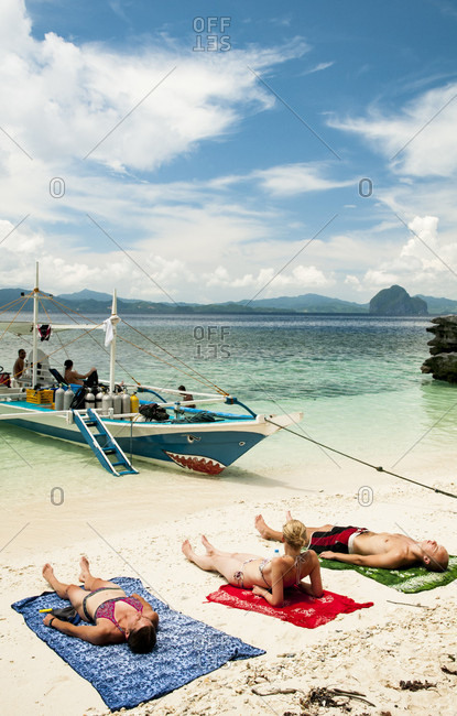 Sun Bathers Relaxing On The Shore Of An El Nido Beach, Palawan, Philippines