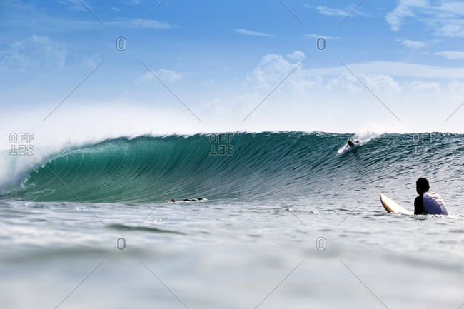A Surfer Look At Another Surfer Surfing On Big Wave